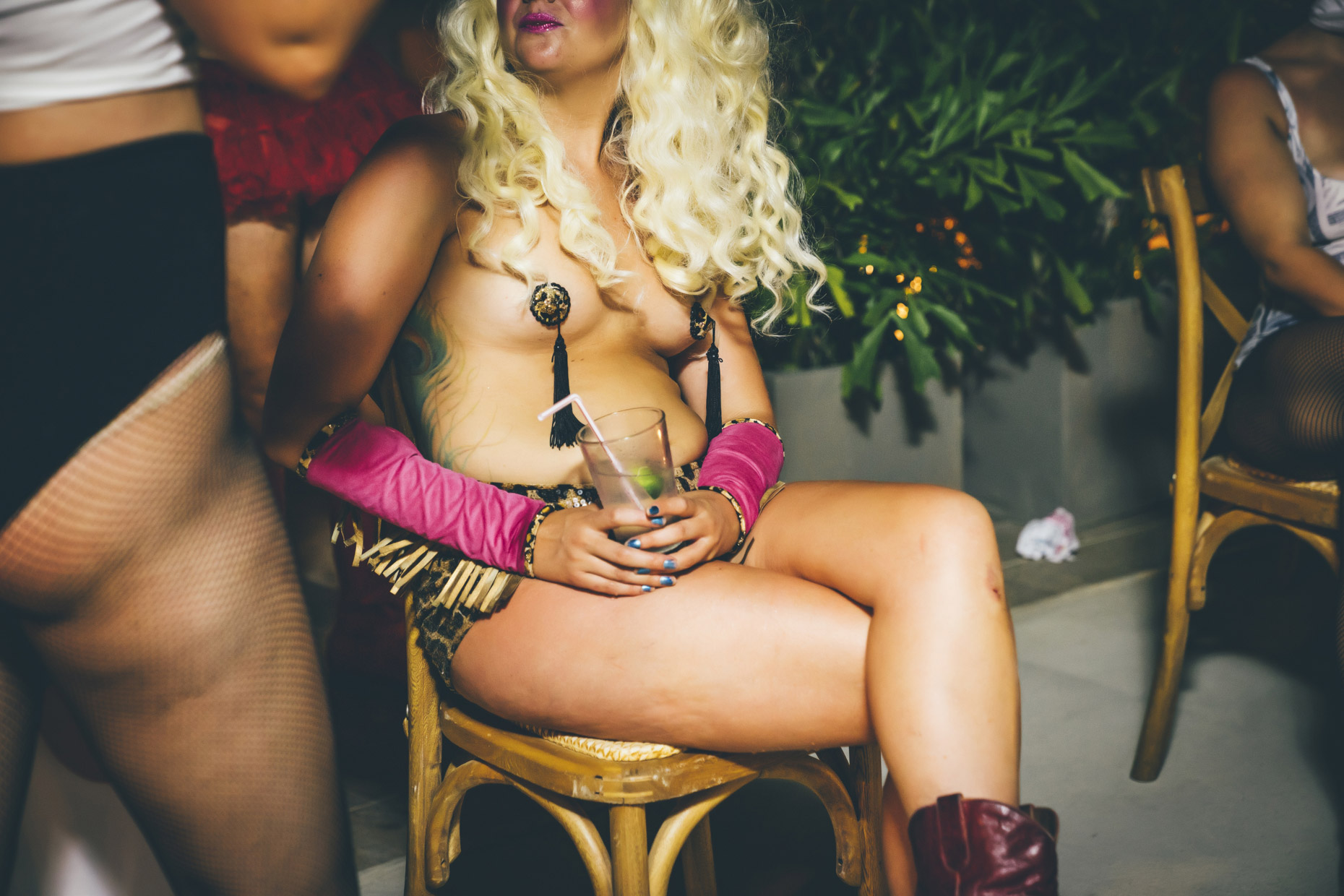 Woman wearing nipple tassles holding cocktail at party