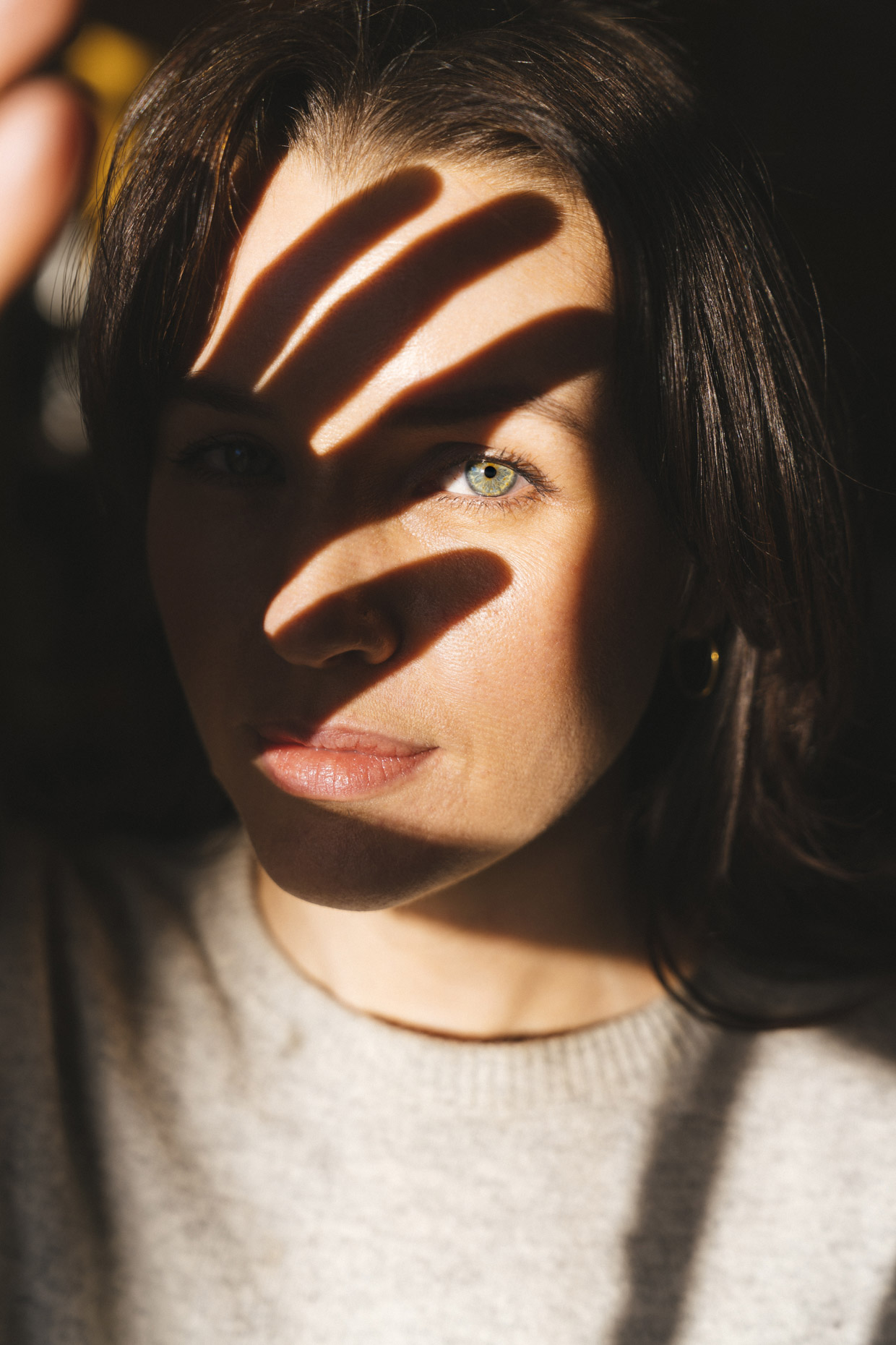 Woman with shadow of hand across face