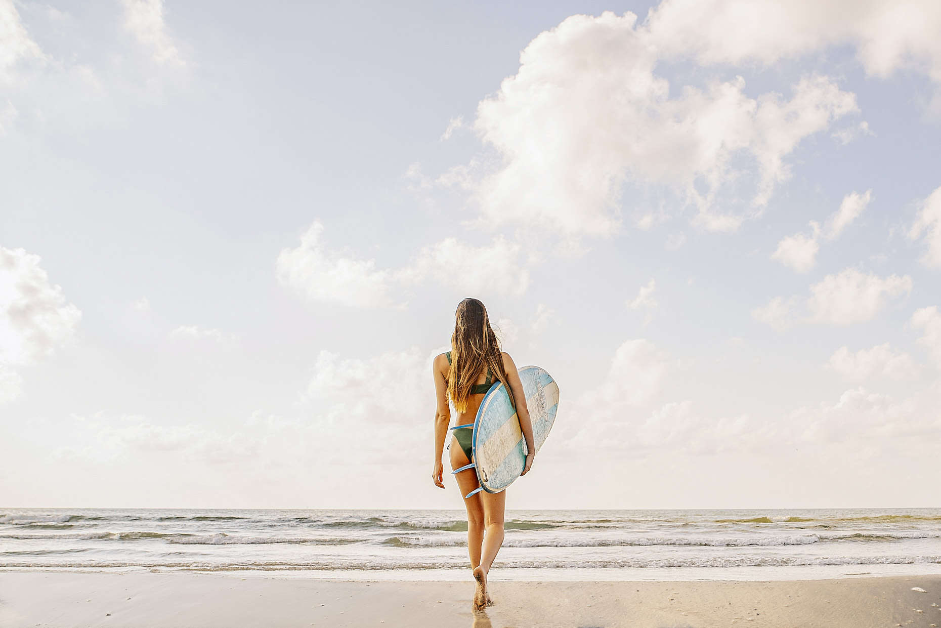 Woman walking with surfboard toward ocean