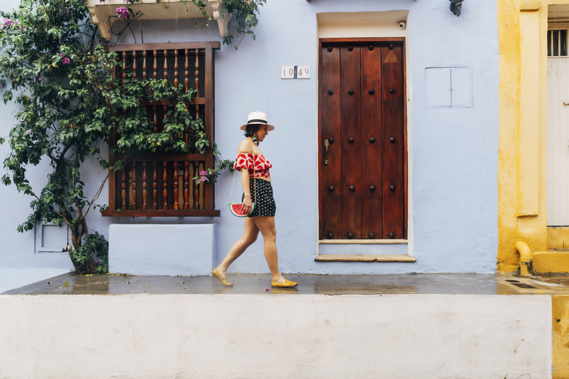 Woman with watermelon purse and top walking  on colorful street in Cartagena, Colombia