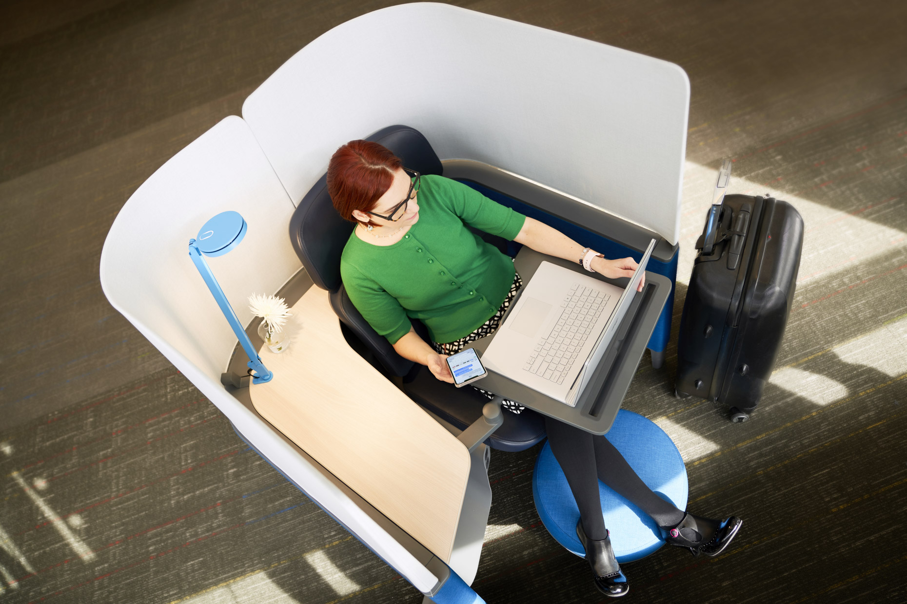 Woman working in privacy pod in airport