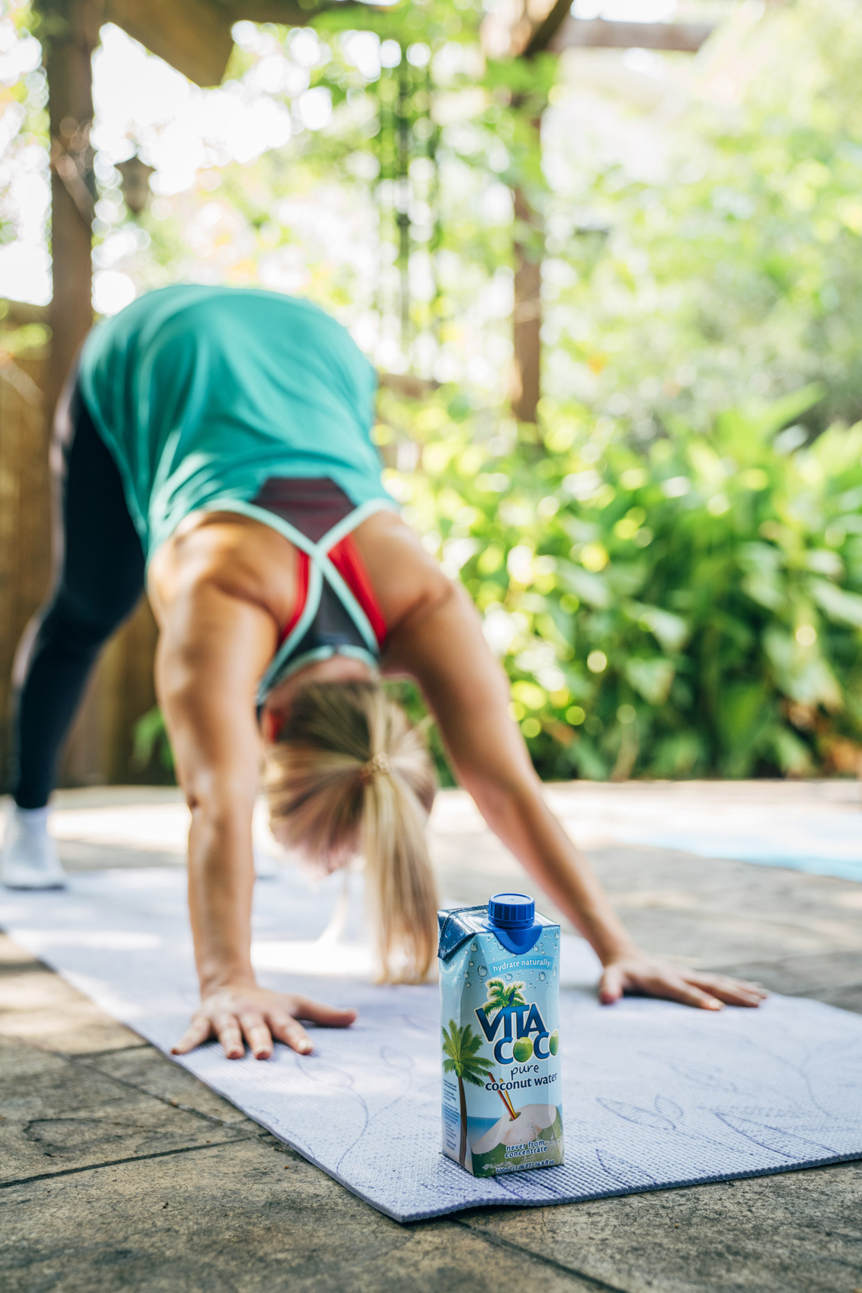 Women doing yoga on mat outside with vita coco coconut water
