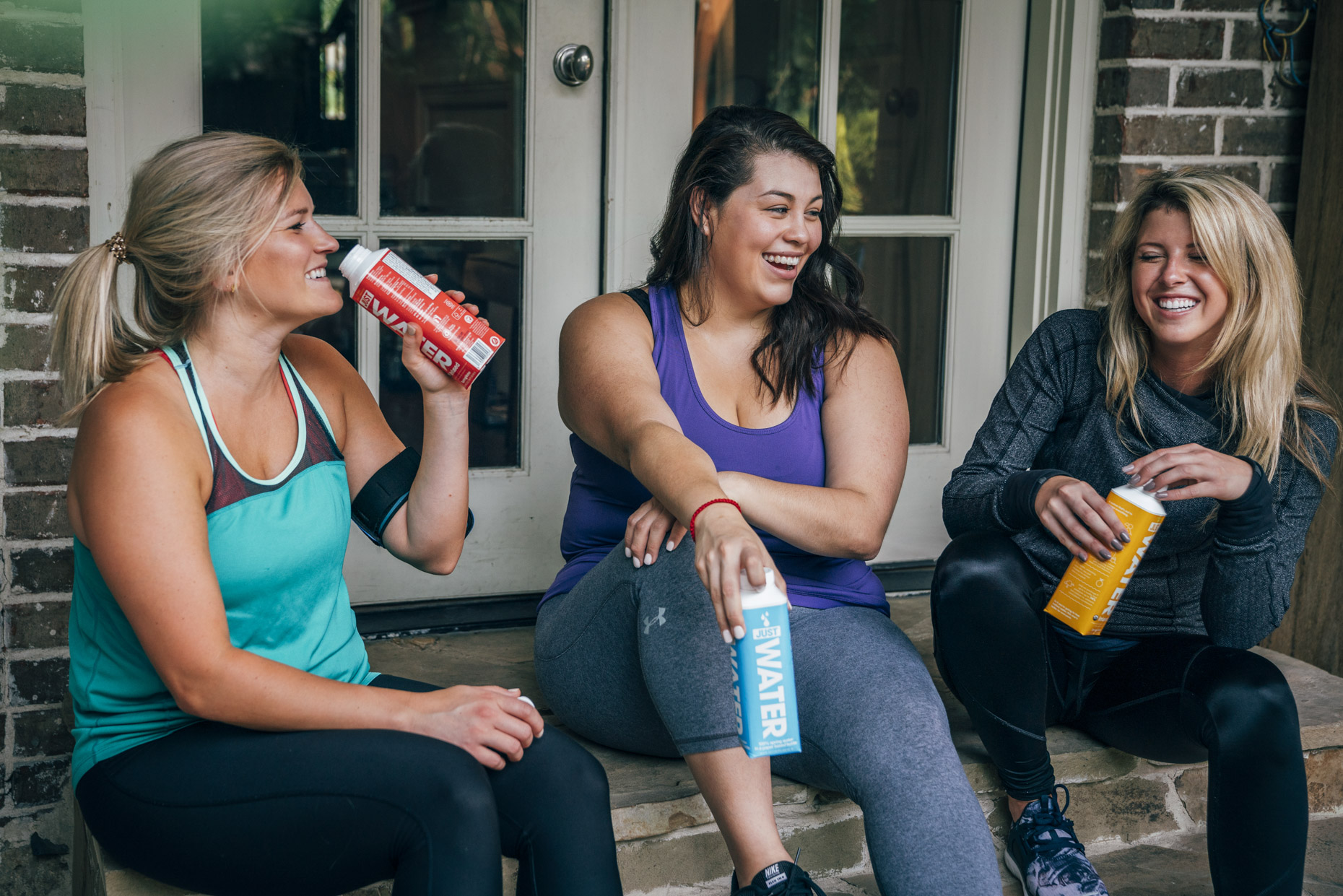 Women sitting on steps outside fitness studio drinking boxed water and laughing