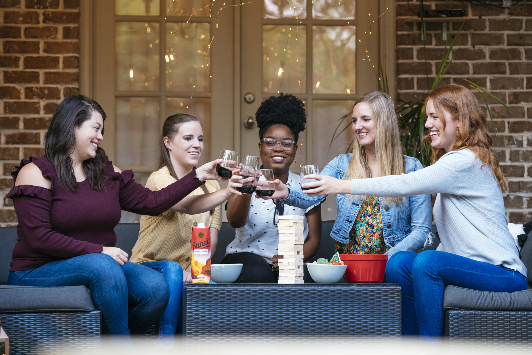 Women toasting with wine at backyard party