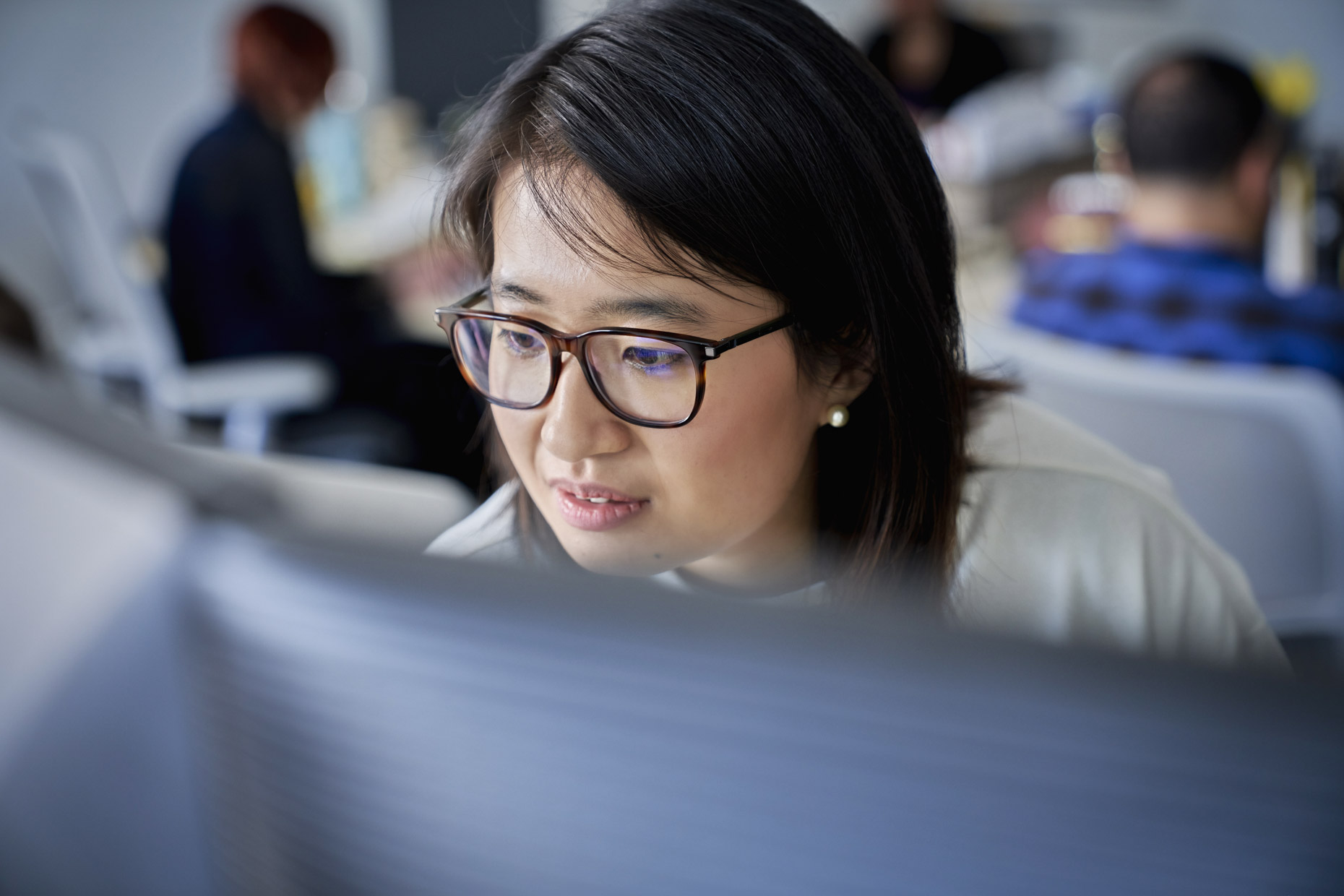Asian woman with glasses working at computer in busy office