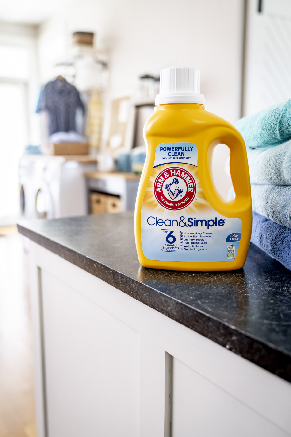 Bottle of Arm and Hammer laundry soap sitting on counter next to towels