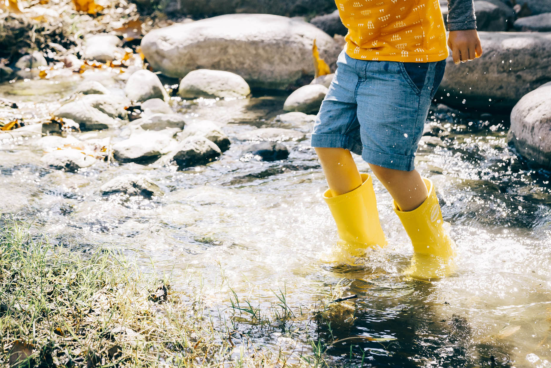 Boy in yellow rubber boots jumping in creek water