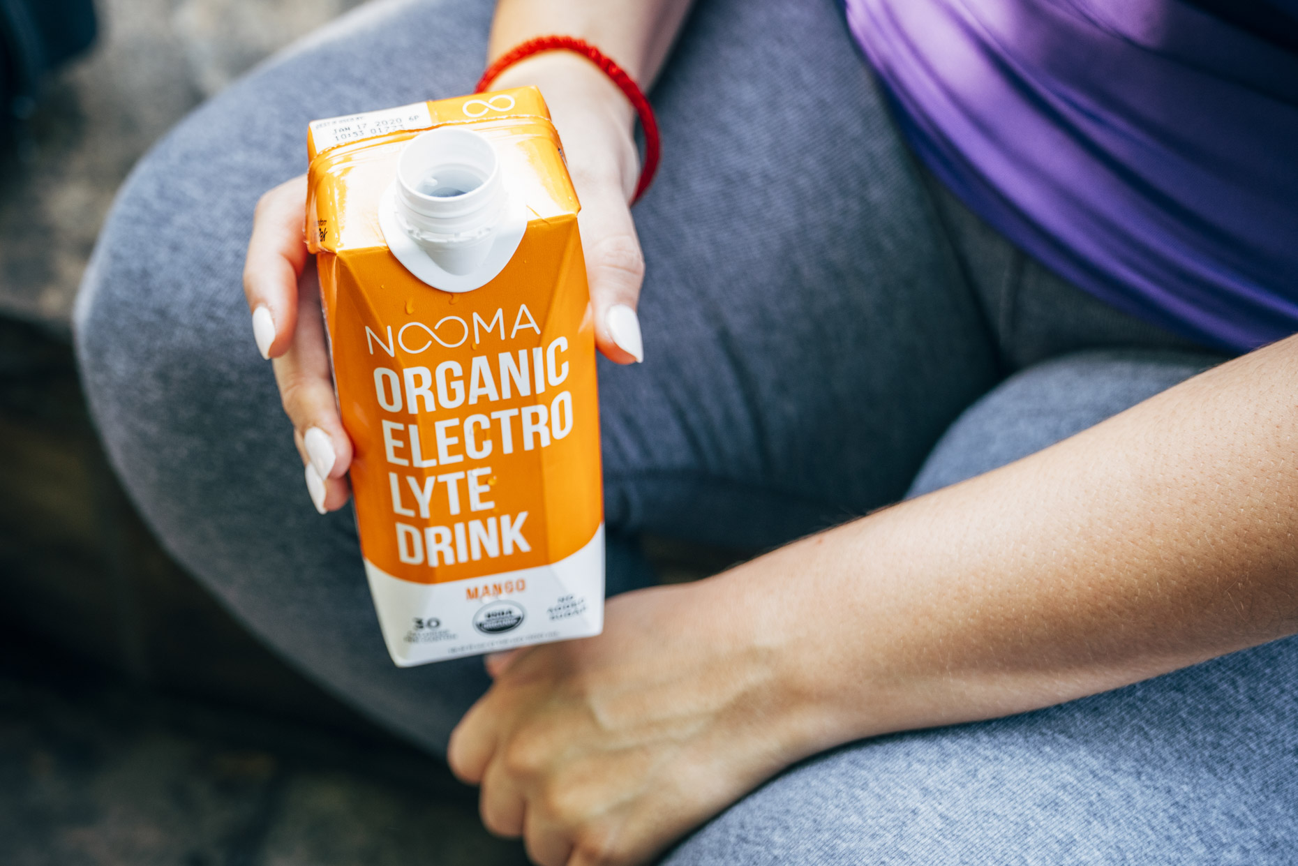 Close up shot of woman in workout clothes holding Nooma mango electrolyte drink