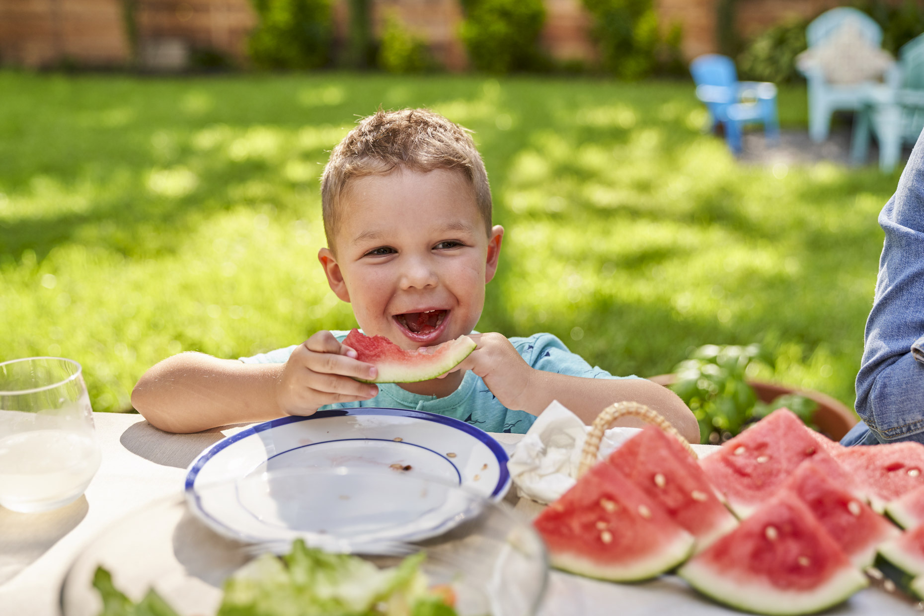 Happy boy eating watermelon at picnic