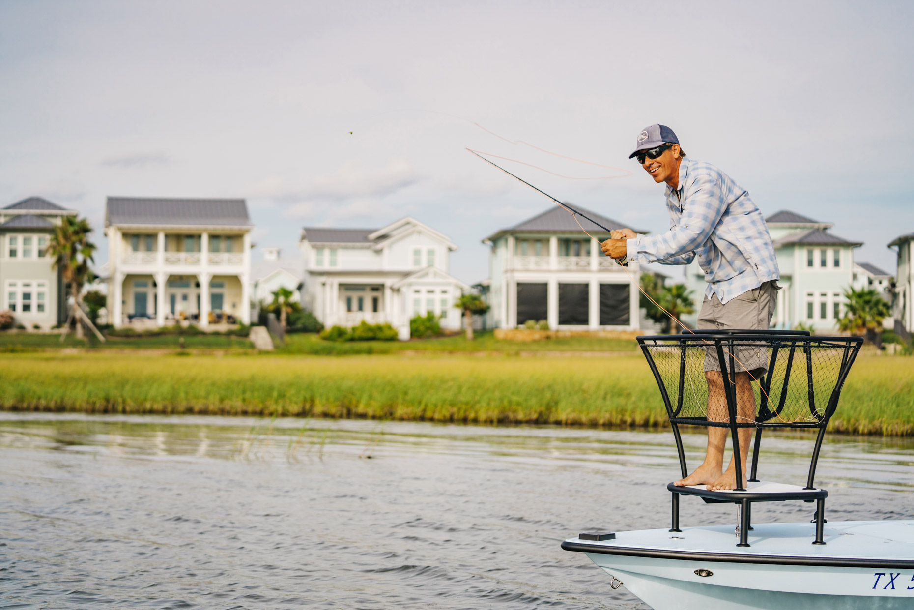 Happy man fly fishing from boat in front of houses