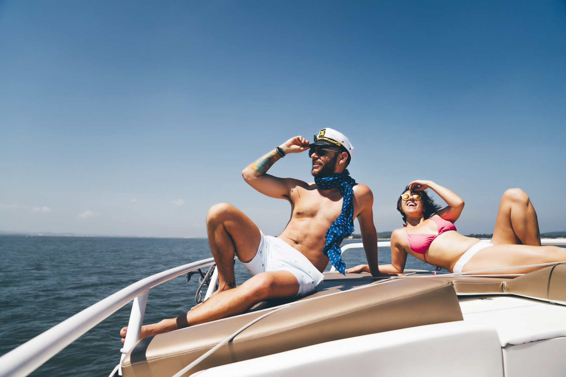 Happy man and woman on yacht sun bathing