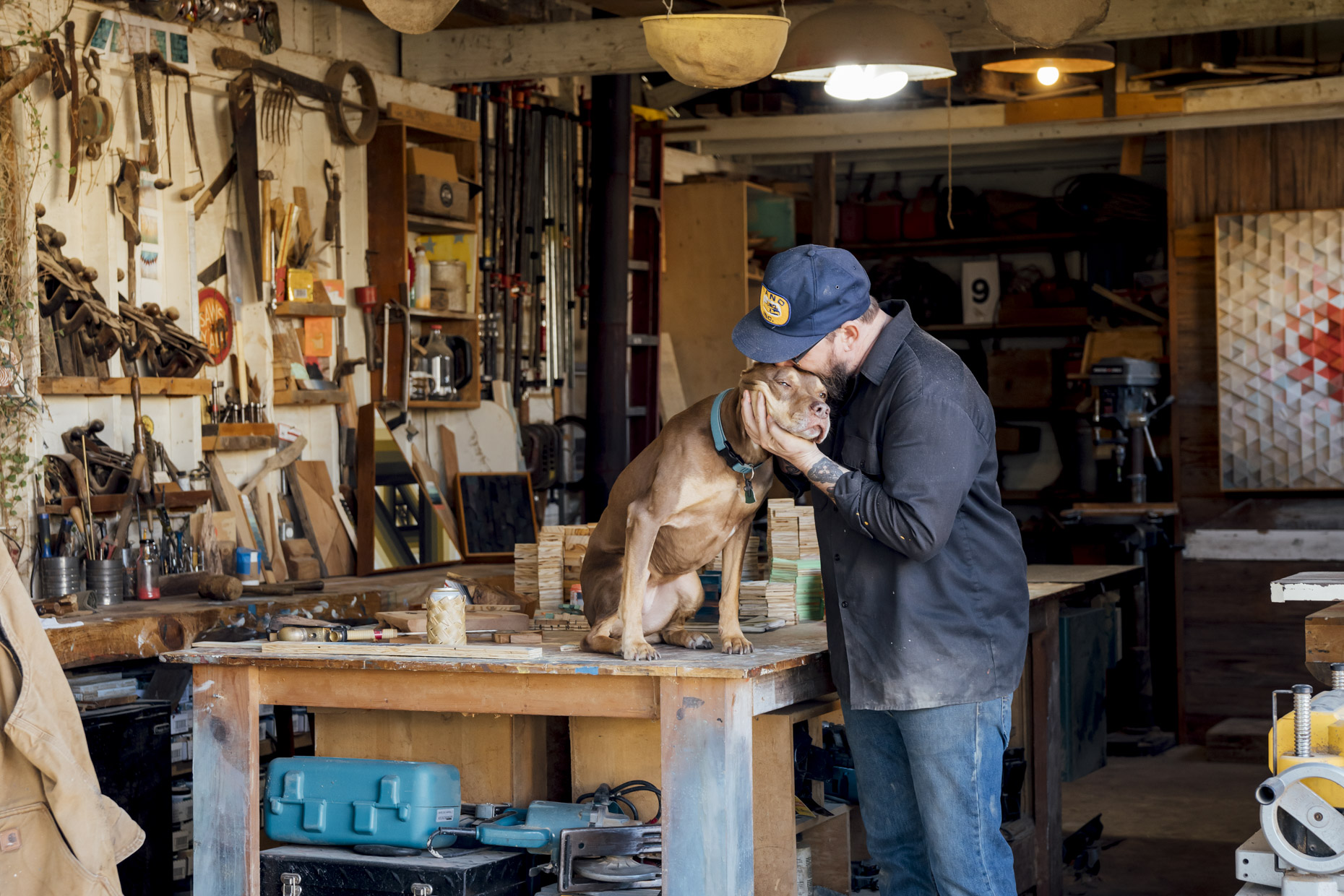 man-in-wood-working-shop-kissing-dog-on-head-Inti-St-Clair-Lifestyle-is201912060209-2