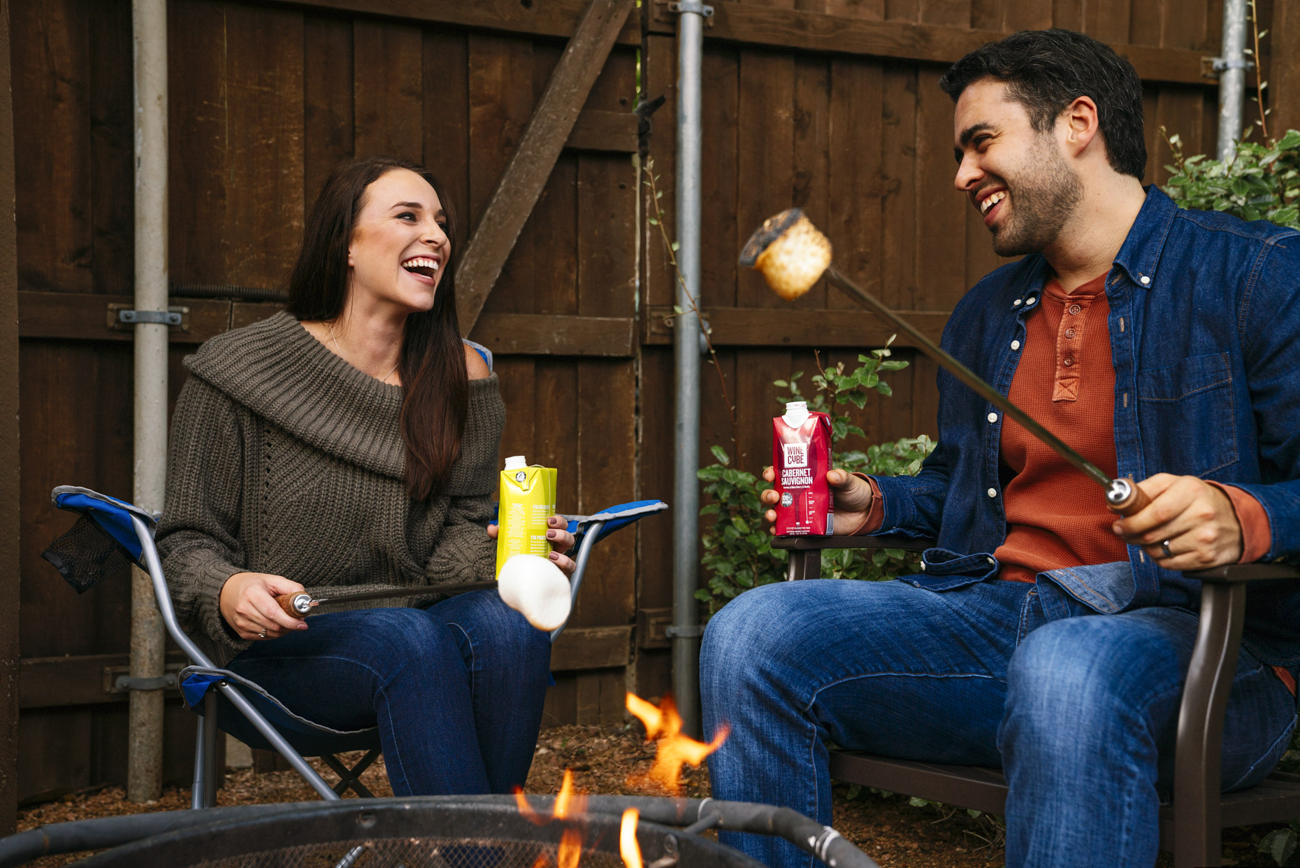 Man and woman roasting marshmallows over fire drinking boxed wine and laughing in back yard
