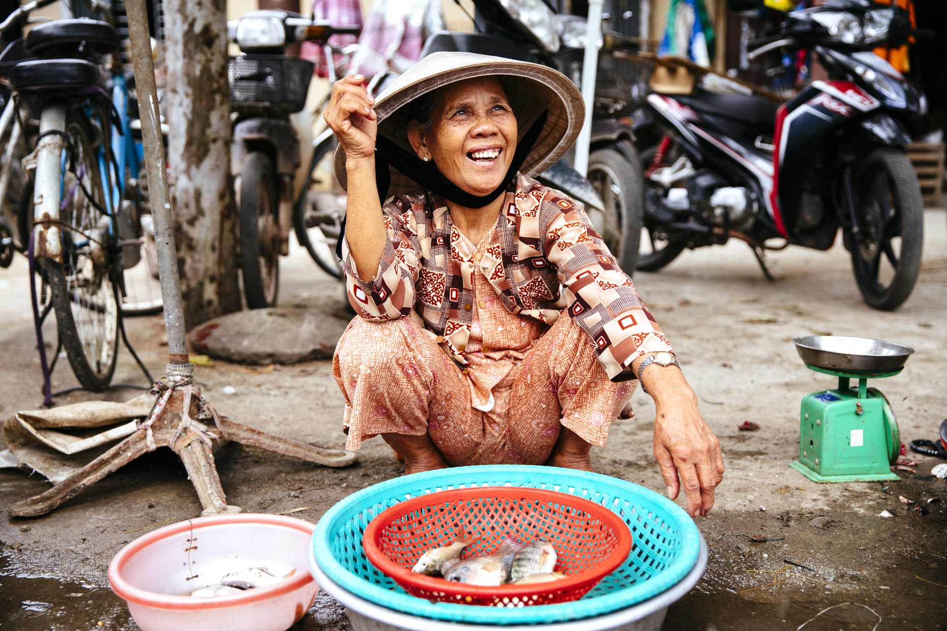 Inti St Clair photo of smiling woman selling fish on sidewalk in Hoi An Vietnam