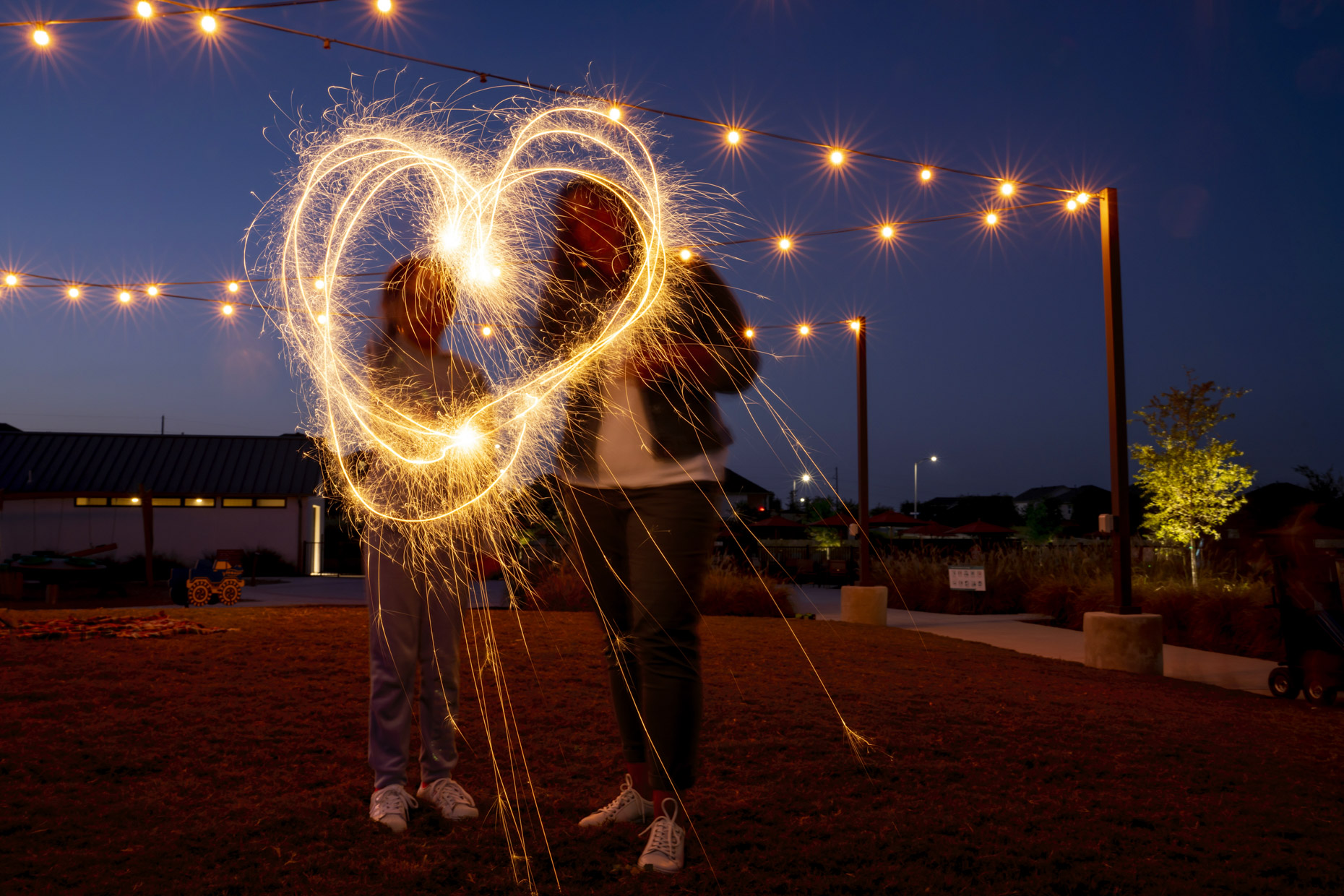 Woman and girl making heart with sparklers at night