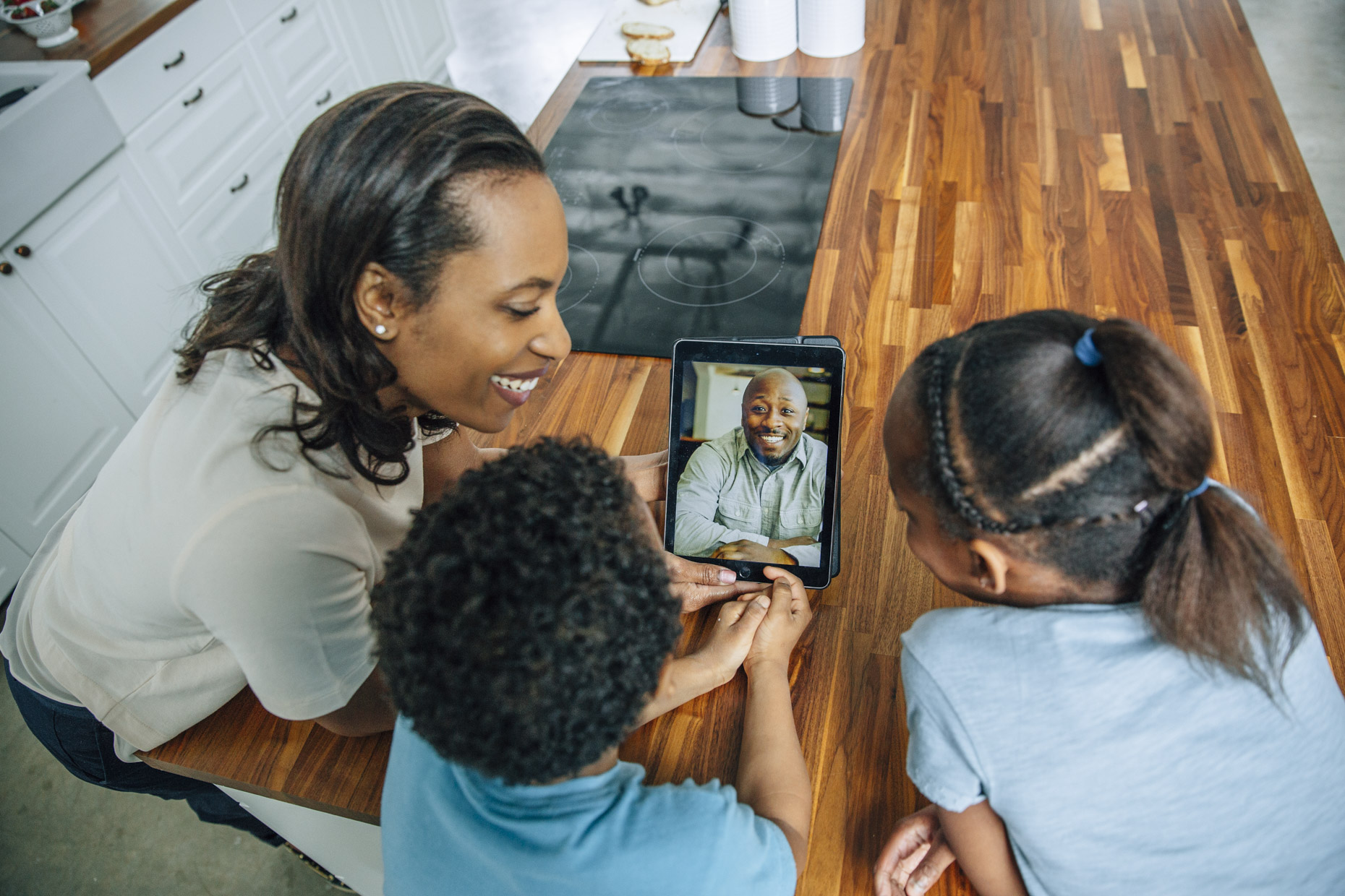 Woman and kids video chatting with dad on iPad tabled computer in kitchen