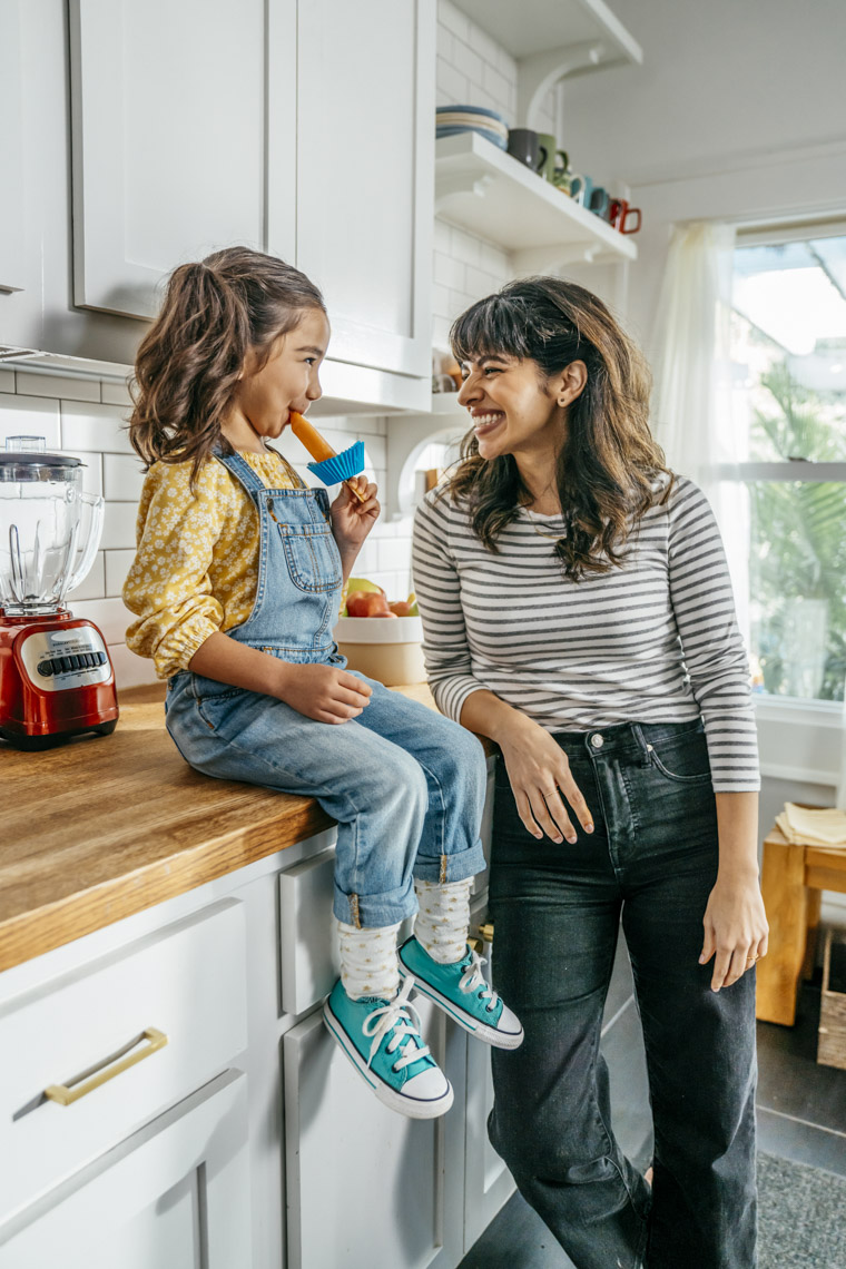 Woman smiling at girl sitting on counter in kitchen eating popsicle