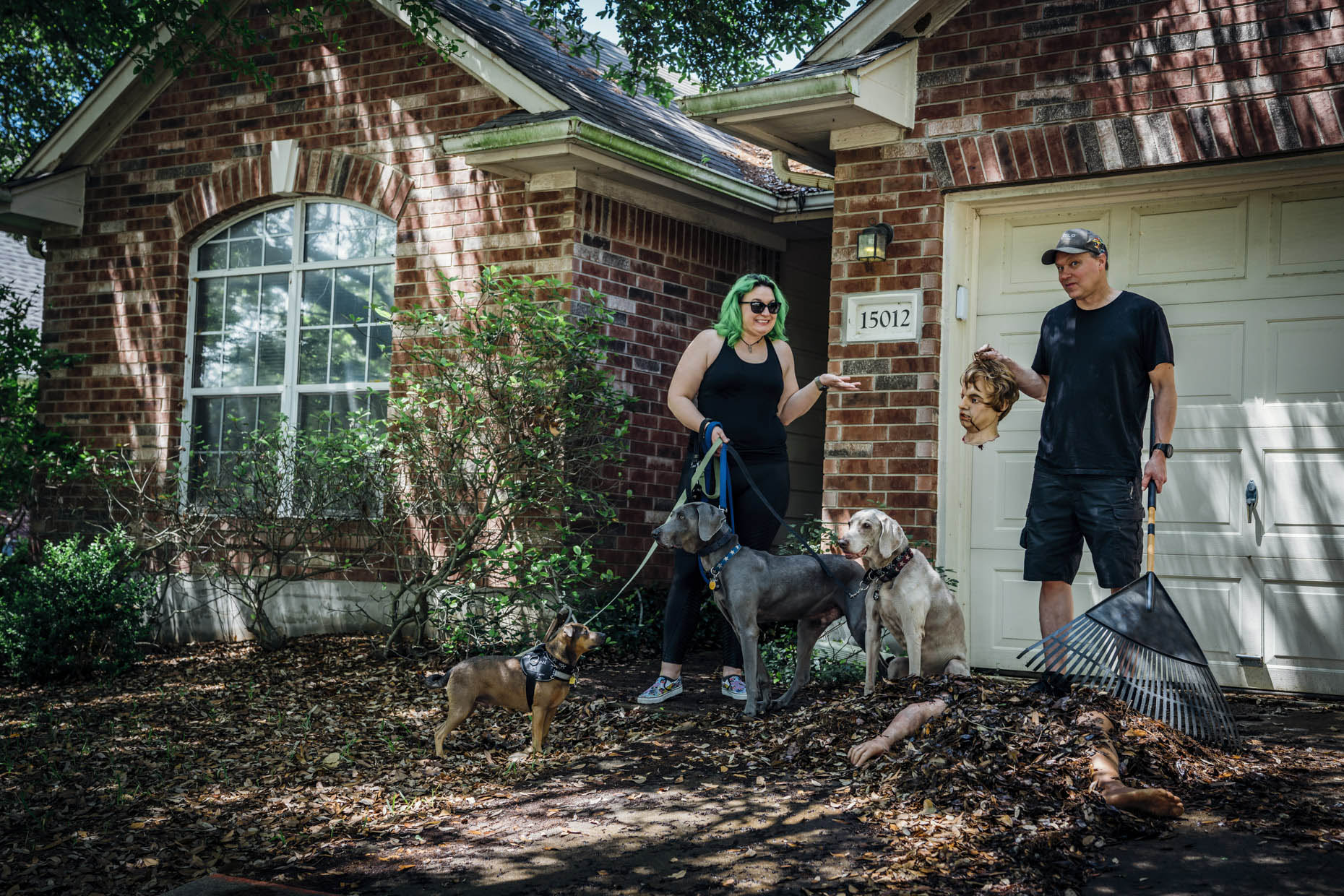 Woman with green hair holding leashes of three dogs next to man holding human head and rake in front of pile of leaves with leg and arm in front of house